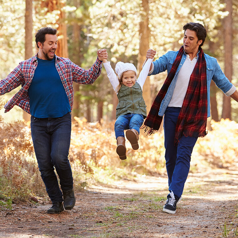 Gay Male Couple With Daughter Walking Through Fall Woodland