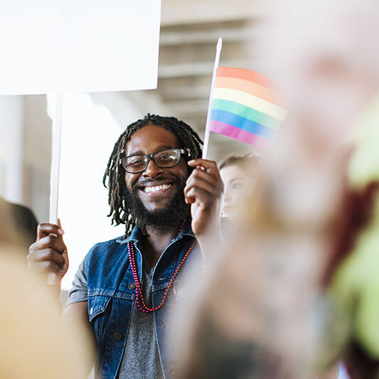 Black man holding a pride flag smiling at the camera